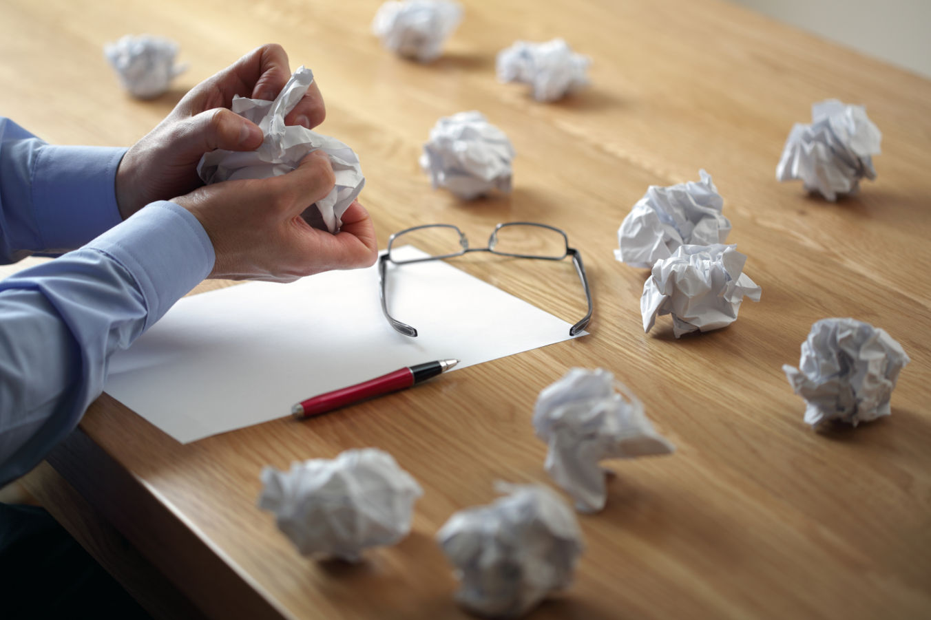 Writer with crumpled paper balls