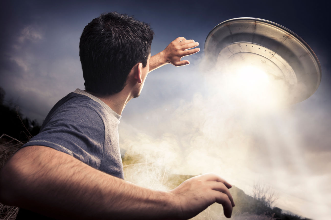 Man staring up at a landing UFO
