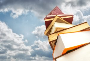 Books stacked against sky