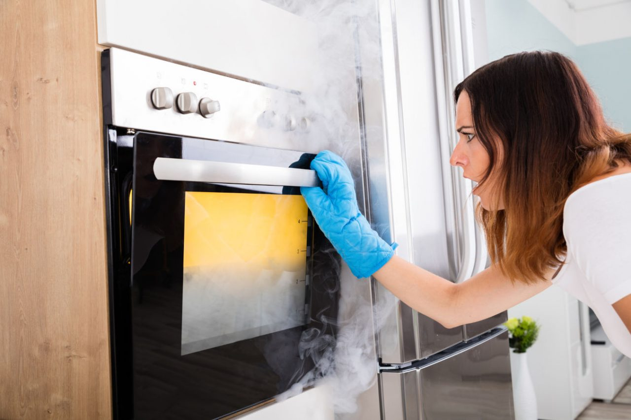 Shocked Young Woman Looking At Smoke Coming Out Of Oven In Kitchen